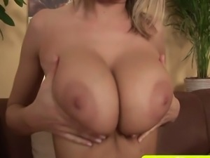 A big boobed blond babe massages her huge natural tits and pussy on the sofa