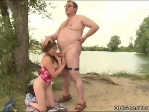 Sex crazed coed with pigtails is having fun with an old fart by the lake