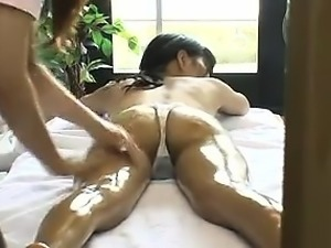 Pretty Asian girl lies on her belly and relishes a relaxing