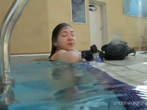 Red haired Roxalana Cheh swimming naked in a pool