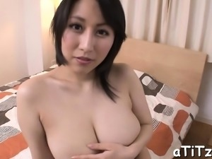 Oriental chick is showing off her melon size love muffins