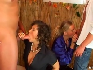 Curly haired Tatiana Milovani and a blonde babe playing with dicks