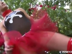 Fancy looking girl Pinky June in red tutu masturbates in the garden