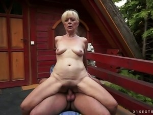Old blonde bitch on the backyard opens her legs for a young man