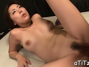 Voluptuous asian stimulates her muff with a strong toy