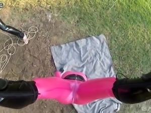 Hanging upside down Lucy Latex has to suck latex cock outdoors