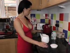 Beautiful brunette babe preparing coffee with downblouse